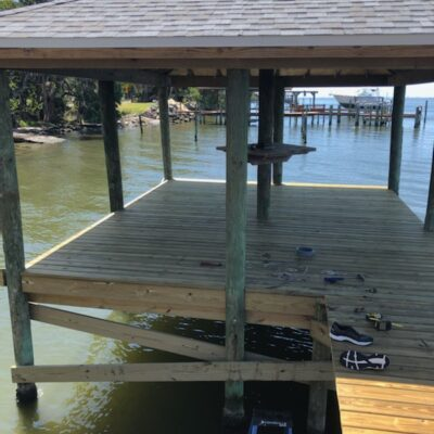 Custom Dock with Shingle Roof covering and standing bar on piling
